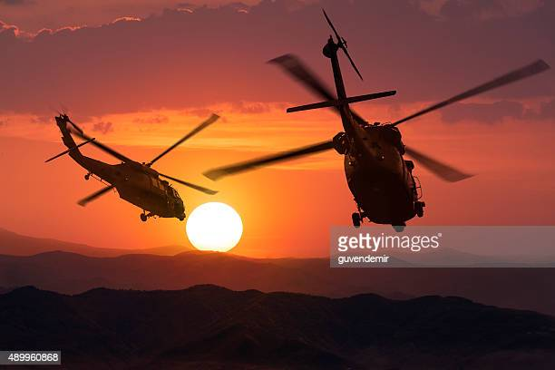 two flying army helicopters on sunset background - military helicopter stock photos and pictures