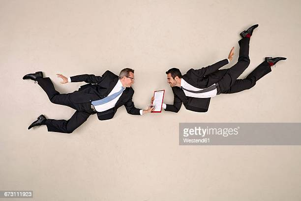 two flying business men signing contract - hovering stock pictures, royalty-free photos & images