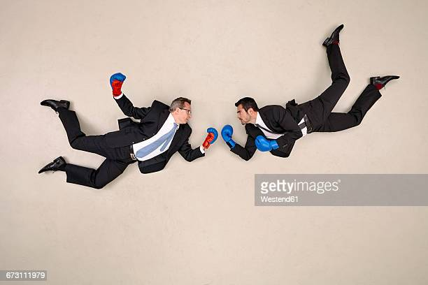two flying businessmen boxing - hovering stock pictures, royalty-free photos & images
