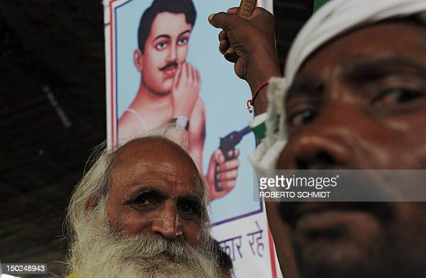 Two followers of Yoga Guru Baba Ramdev stand in front of a placard depicting Indian Independence freedom fighter and hero Chandra Shekhar Azad during...