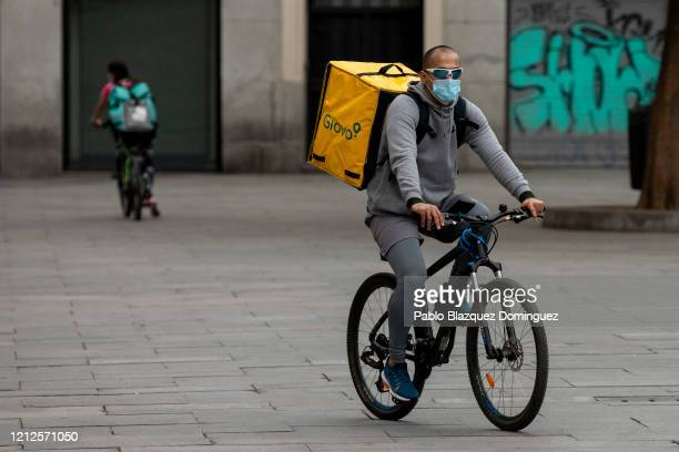 Two food couriers wearing protective masks ride their bikes along Callao Square on March 15, 2020 in Madrid, Spain. Madrid has so far reported 2,807...