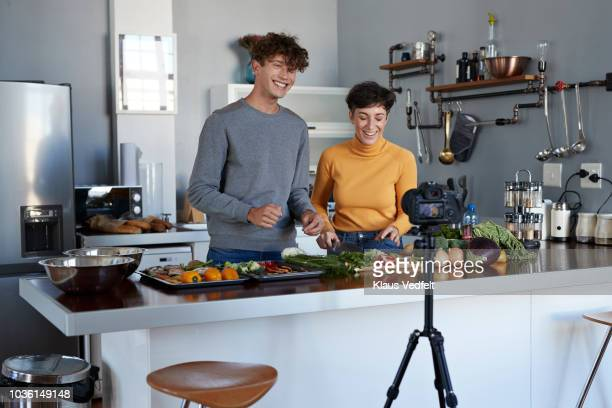 two food vloggers making video while prepping vegetables in kitchen - vlogging stock pictures, royalty-free photos & images