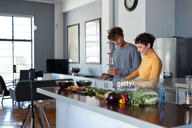 two food vloggers making video while prepping vegetables in kitchen - kitchen counter stock photos and pictures