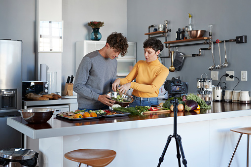 Two food vloggers making video while prepping vegetables in kitchen - gettyimageskorea