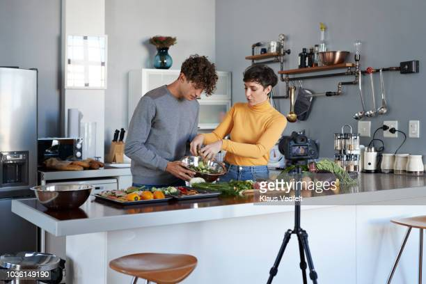 two food vloggers making video while prepping vegetables in kitchen - wife stock pictures, royalty-free photos & images