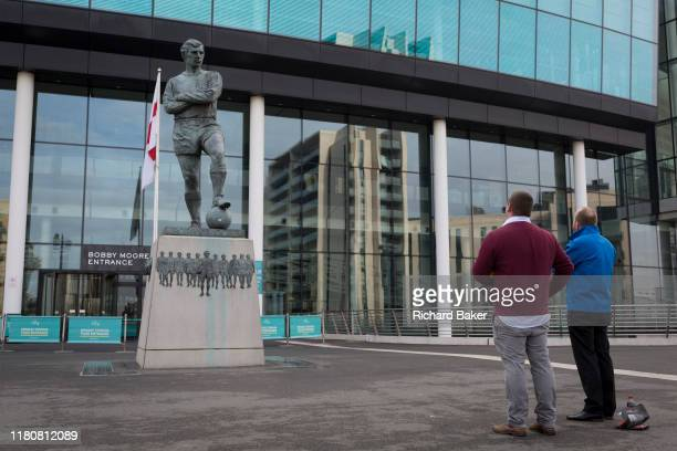 Two football fans pay their respects to the statue of English football's most loved player, Bobby Moore, on 6th November 2019, in Wembley, London,...