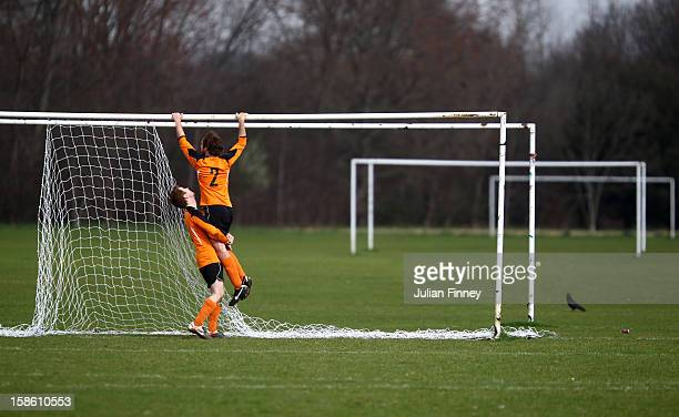 Two football players attempt to take the goal net down after their match at Hackney Marshes on March 18, 2012 in London, England. Hackney Marshes in...
