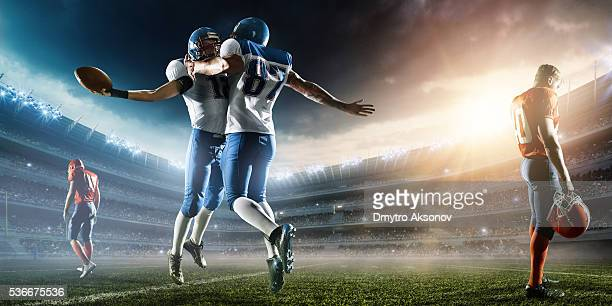 two football players celebrate their victory - quarterback stock photos and pictures