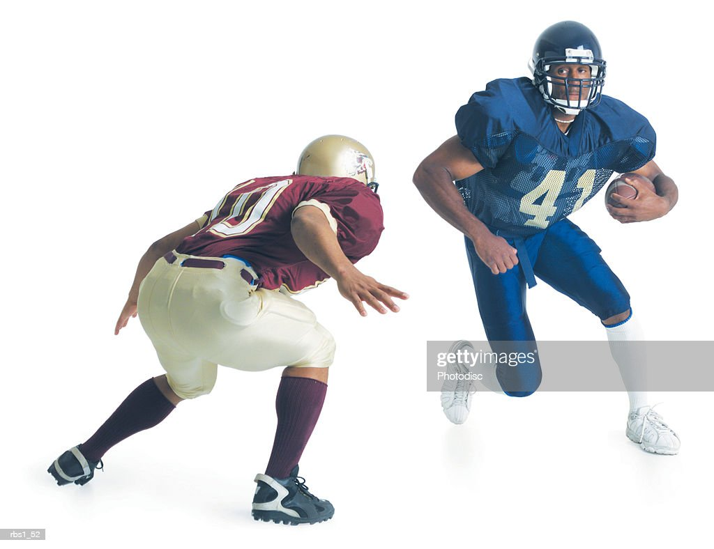 two football players from opposing teams are running towards each other as one holds the football and the other crouches forward to stop him : Foto de stock