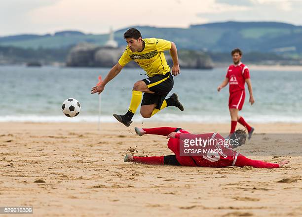 Two football players vie during the 52nd Football Championship Santander beach football amateur match on the beach of the Sardinero of Santander...
