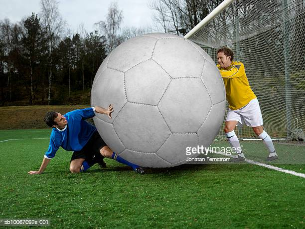 two football players with oversized ball - man with big balls stock photos and pictures
