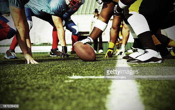 two football teams meet at the line of scrimmage - football stockfoto's en -beelden