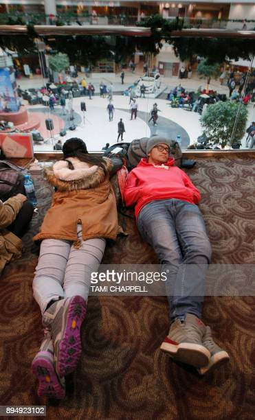 Two foreign exchange students rest above the airport atrium as they wait on another flight the day following a power outage caused by a fire at...