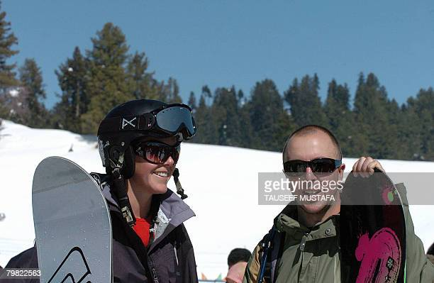Two foreign snowboarders pause as they watch an event at the ski resort of Gulmarg on February 18 2008 The ski resort was abuzz with activity as...