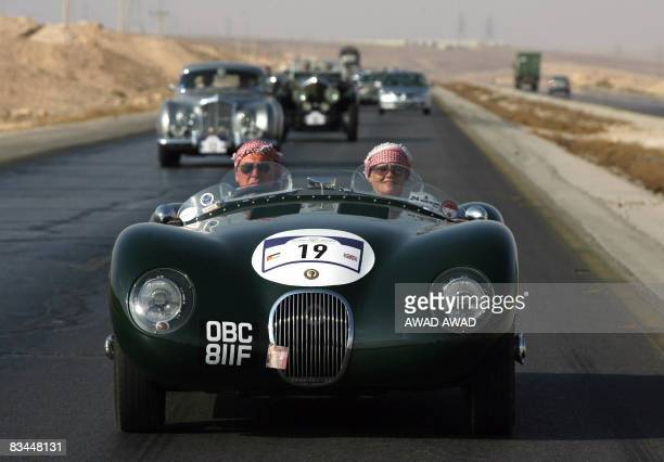 Two foreigners wear Arab headscarves in a 1968 Jaguar Proteus CType classic car during a rally tour in the central Jordanian city of Kerak on October...