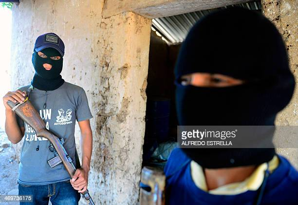 Two former punteros of the Templar Knights drug cartel pose during an interview with AFP at la Nopalera community Michoacan state Mexico on February...
