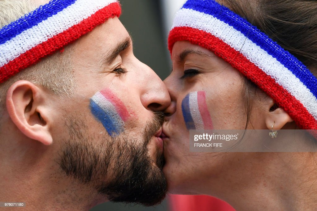 Two France fans kiss each other before the Russia 2018 World Cup Group C football match between France and Australia at the Kazan Arena in Kazan on June 16, 2018. (Photo by FRANCK FIFE / AFP) / RESTRICTED