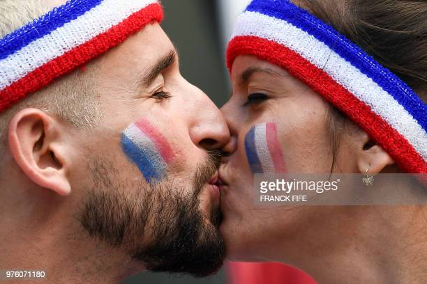 Two France fans kiss each other before the Russia 2018 World Cup Group C football match between France and Australia at the Kazan Arena in Kazan on...