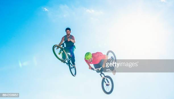 Two freestyle cyclists in mid-air