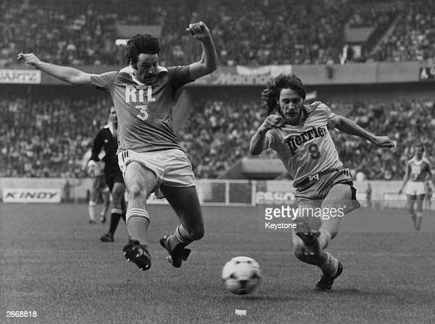 Two French footballers running for the ball during the French Cup final between Auxerre and Nantes.