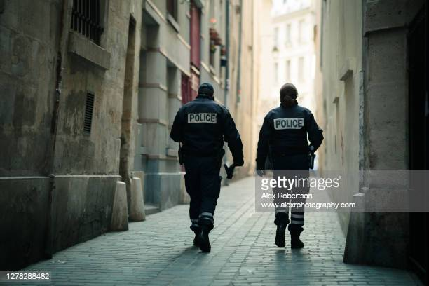 two french police officers patrol a paris alleyway - france stock-fotos und bilder