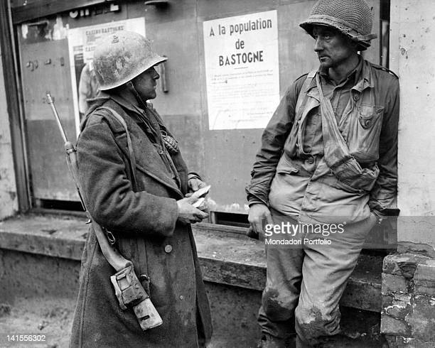 Two French soldiers in discussion in front of a poster addressed to the population during the German advance in the Ardennes Bastogne 19th December...