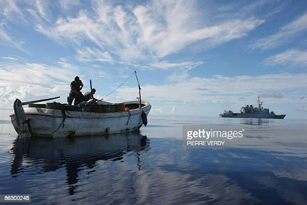 Two French soldiers inspect the boat that held three pirates who where captured early this morning and taken to the French warship 'Nivose' in the...