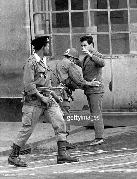 Two French soldiers members of the Foreign Legion frisk an Algerian civilian in the ancient Casbah in the heart of Algiers during the fighting...
