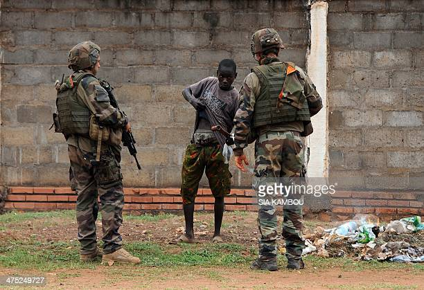 Two French soldiers part of the Sangaris operation frisk a young man in the PR4 district of Bangui on February 27 2014 The Central African Republic's...