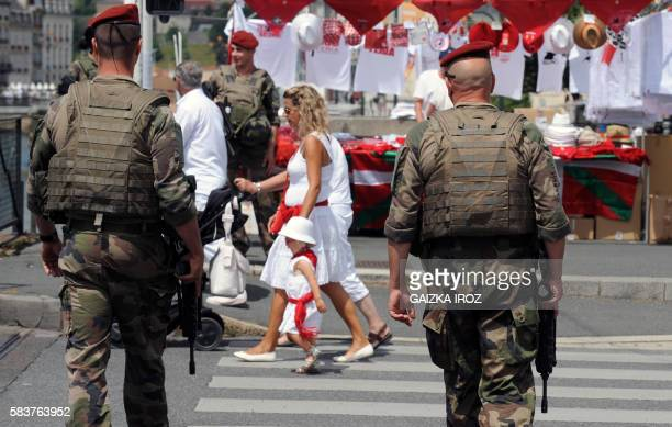 Two French soldiers patrol as tourists walks along street stalls in Bayonne southwestern France on July 27 2016 during the typically Basque Bayonne...
