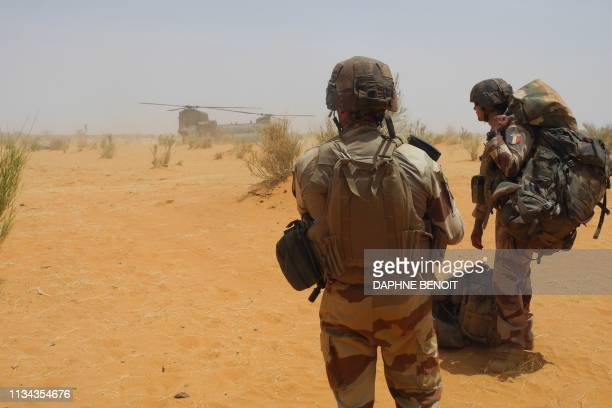 Two French soldiers wait to embark aboard of a British Chinook helicopter nearby the new French military base of Gossi in center Mali on March 24...