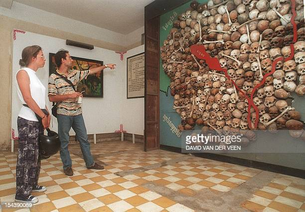 Two French tourists on 20 June inspect a map made of skulls of some of the victims of the Khmer Rouge regime at Tuol Sleng museum a school that was...