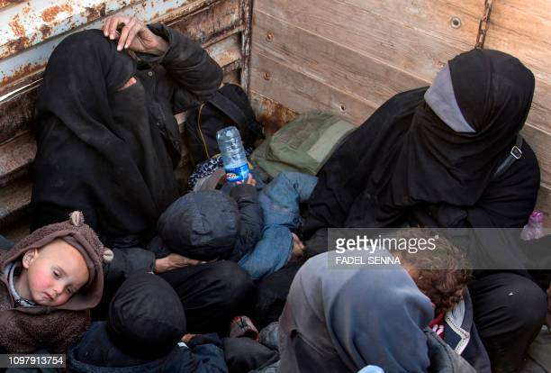TOPSHOT Two French women who fled the last Islamic State group's tiny pocket in Syria sit in the back of a truck near Baghuz eastern Syria on...