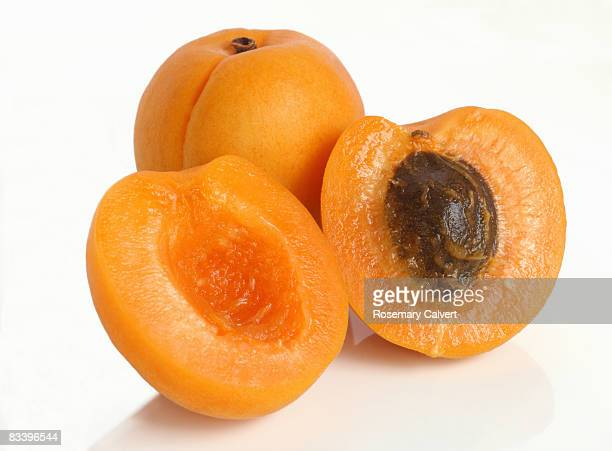 Two fresh apricots, one cut in half.