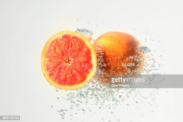 two fresh grapefruits in water with air bubbles isolated on white background - image stock pictures, royalty-free photos & images