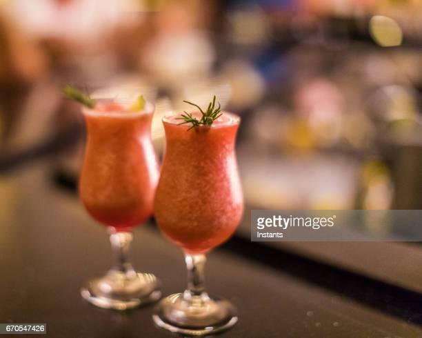 バーの設定タイムの小枝やライムのスライスで飾られた 2 つの新鮮なイチゴ daiquiris カウンターと満喫する待っています。