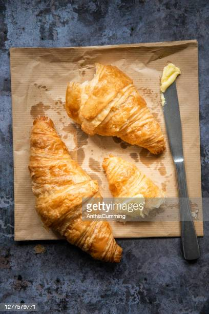 two freshly baked french croissants with butter and a knife - cross section stock pictures, royalty-free photos & images