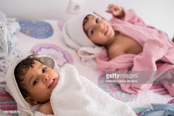 two freshly showered toddlers wrapped in a towel on top of their home bed - ハイキー ストックフォトと画像