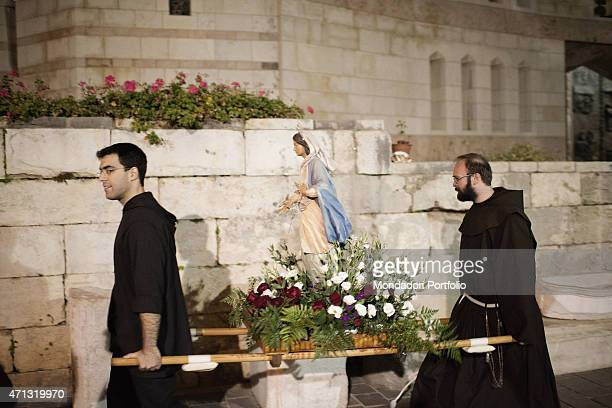 Two friars carry a Madonna's statue out of Basilica of The Annunciation Nazareth