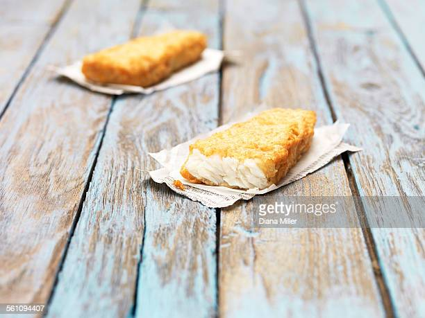 Two fried chunky battered haddock pieces on wooden table