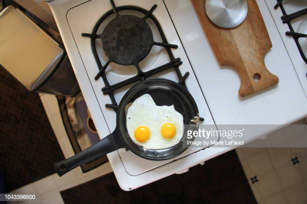 Two fried eggs cooking on a stove top