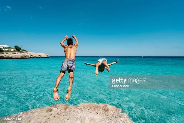 dos amigos se zambullyn en el mar desde un acantilado - mar caribe fotografías e imágenes de stock