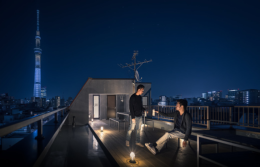 Two friends are hanging out on the rooftop with Tokyo Skytree at the background - gettyimageskorea