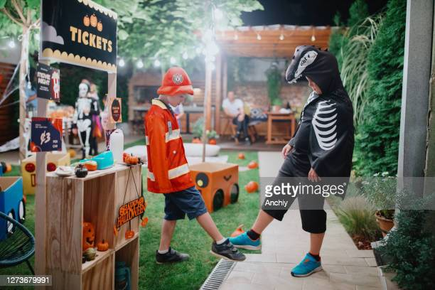 two friends are practicing social distancing and foot tapping as an alternative to handshake - scaredastronaut stock pictures, royalty-free photos & images
