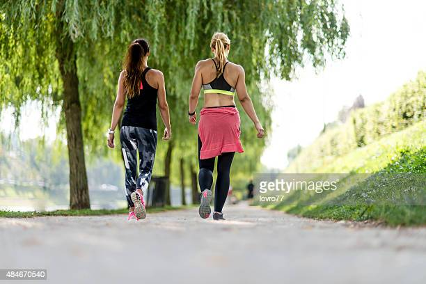Two friends are walking through the park in the city