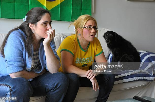 Two friends are watching the fifa 2014 Worldcup match between brazil x chile at home with the dog