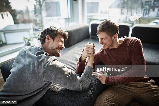 Two friends arm wrestling living room