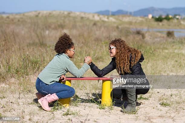 Two friends arm wrestlking outdoors