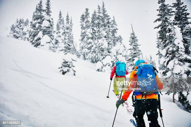two friends ascending mountainside on backcountry ski tour - back country skiing stock pictures, royalty-free photos & images