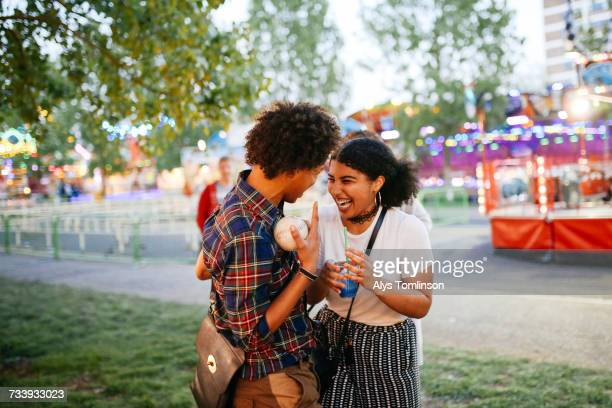 two friends at funfair, laughing, boy holding ball - flirting stock pictures, royalty-free photos & images